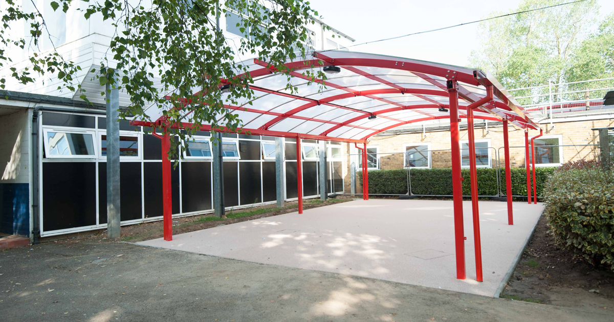 A canopy with polycarbonate sheeting installed outside a building.