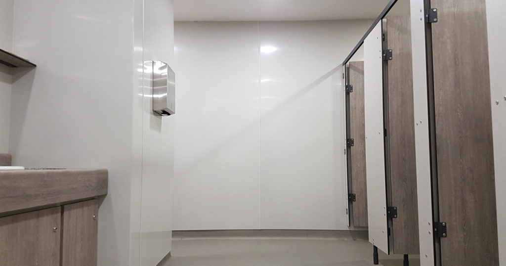 Hygienic wall cladding installed in a white bathroom with cubicles on the right.