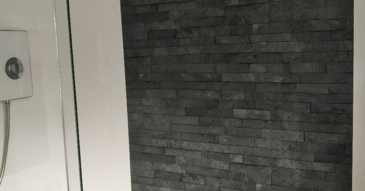 Decorative wall cladding with a grey stone effect installed in a shower area