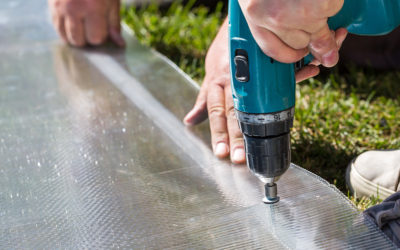 Worker screwing screw into polycarbonate plastic flat sheet. Building greenhouse
